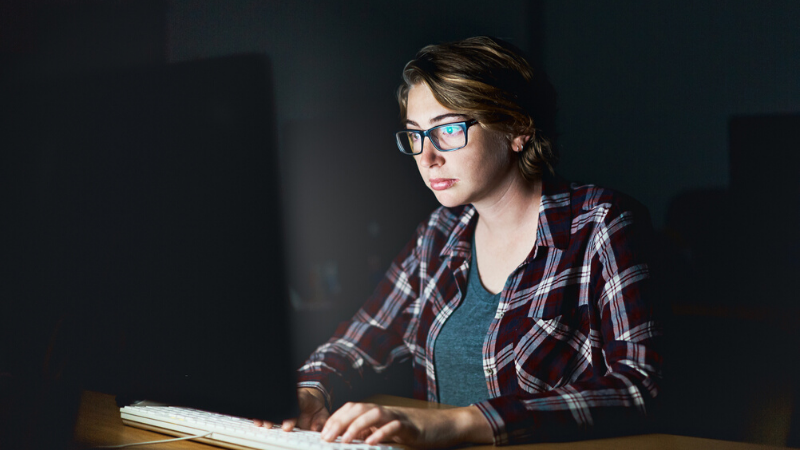 A young woman working by the light of her computer monitor looks serious