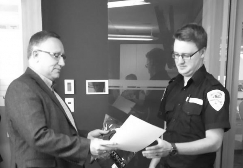 Edmonton Airports Director of Safety & Security, Jason Sangster, presents GardaWorld Security Officer, Aaron Wray with a certificate.