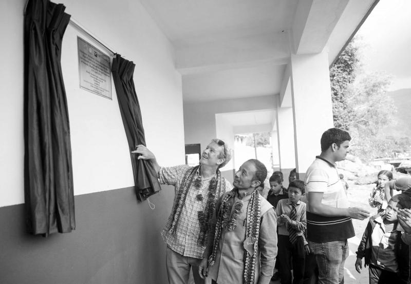 Two men unveil a plaque at the new Niranjana high school in Milanbazar, rebuilt after the Nepal earthquake.