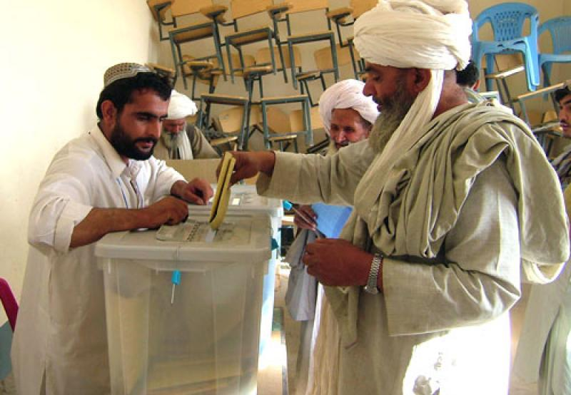 An Afghan man casts his ballot at a polling station in Lashkar Gah, Helmand Province, September 18, 2005. (This image is a work of a U.S. Army soldier or employee, taken or made as part of that person's official duties. As a work of the U.S. federal government, the image is in the public domain.)