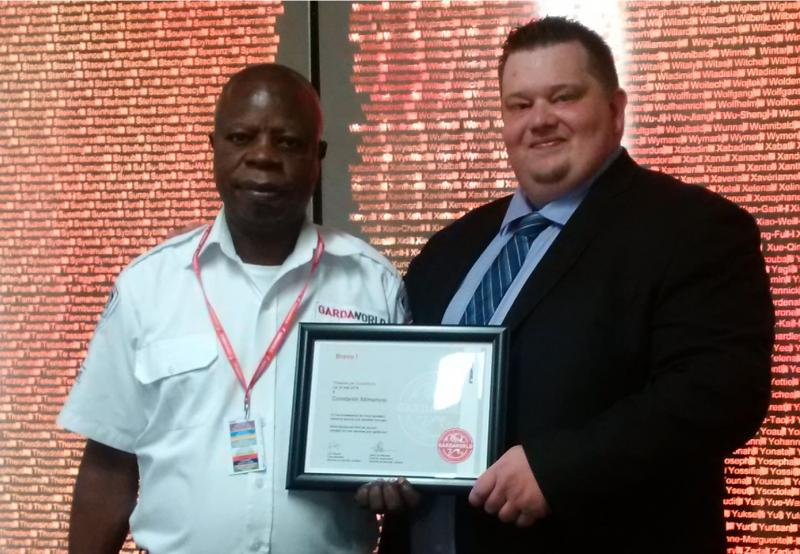 Cédric Dyèvre, Account Manager responsible for GardaWorld security services at the Centre Hospitalier de l'Université de Montréal (CHUM) presents Ntimamosi Constantin a certificate to acknowledge his exceptional customer service