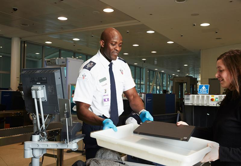 Airport security screening officer with passenger