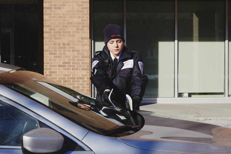 Security guard distributing parking ticket