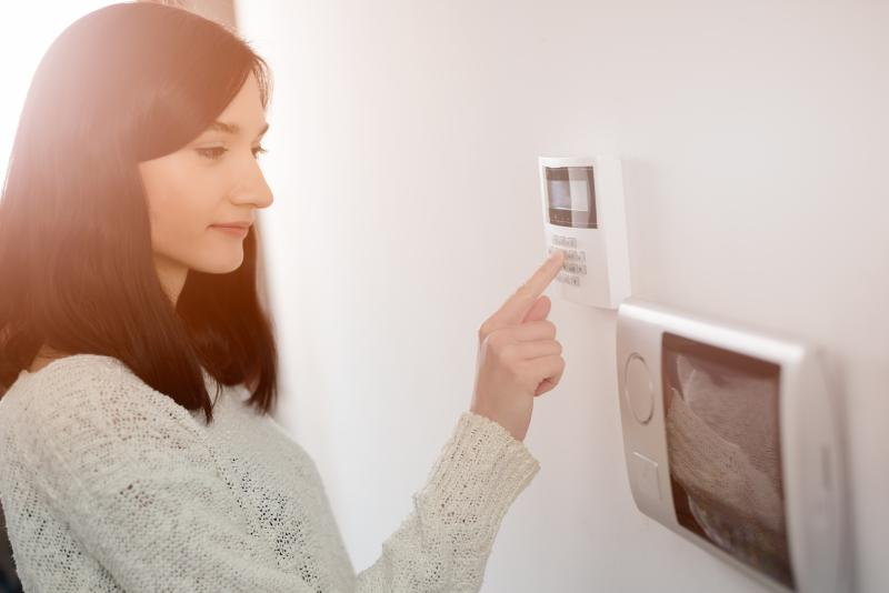A woman enters a code on a security system keypad