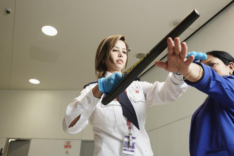 A GardaWorld airport security services professional performs a pre-board screening