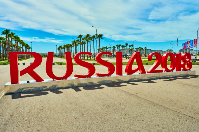"The ""Russia 2018"" sign for the FIFA World Cup set in front of rows of palm trees on a beautiful day"