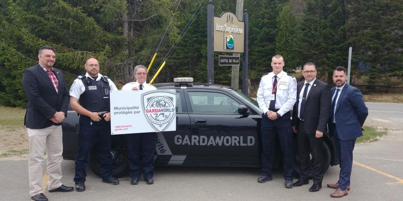 A team of GardaWorld professionals who support police in Lac-Supérieur, Quebec stand in front of a GardaWorld vehicle