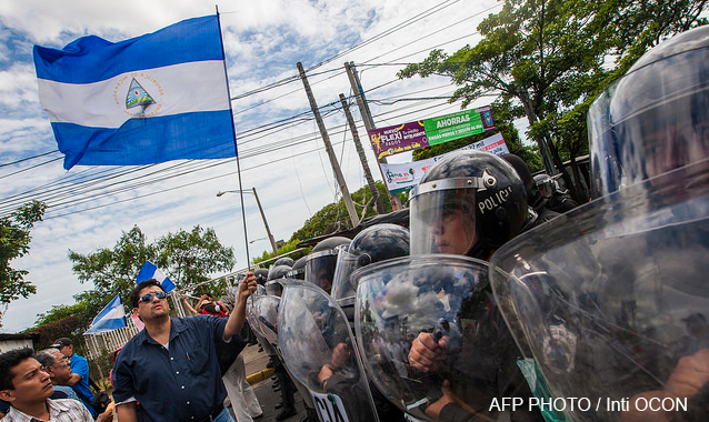 People flutter Nicaraguan national flags in front of a line of riot policemen as they protest against the electoral system in Managua, Nicaragua on July 15, 2015. AFP PHOTO / Inti OCON