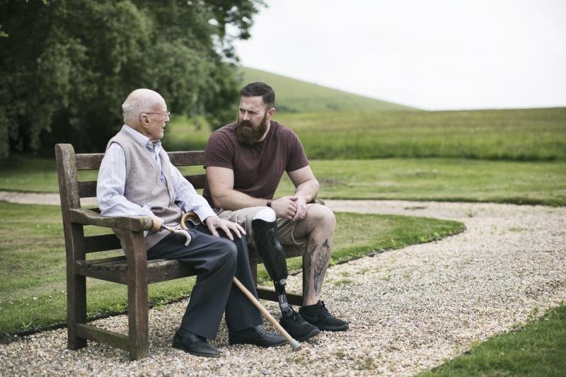 A young veteran with a prosthetic leg sits on a park bench talking to an elderly veteran with a prosthetic arm, as part of a Blesma program that offers help to veterans