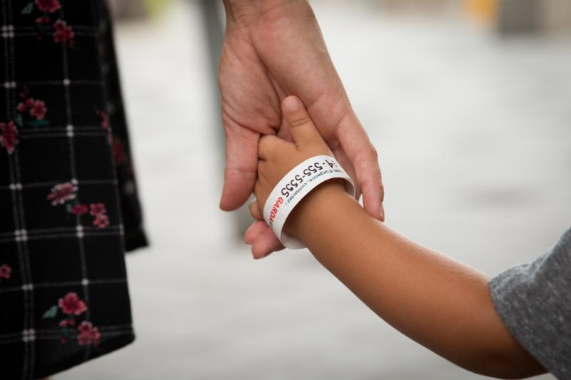 woman holdingthe hand of a child that's wearing a gardaworld bracelet